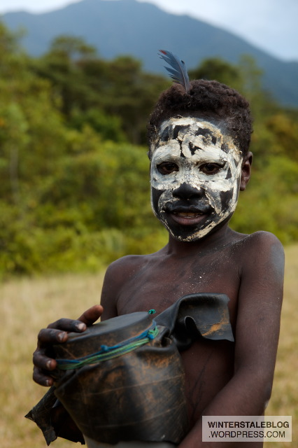 Old mixes with new - this child with the skeleton like black/white face paint is holding a drum made from a section of drainpipe and rubber sheeting (probably a development project leftover from somewhere in the region). Traditionally this drum would most likely have been wooden body with stretched crocodile skin.